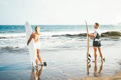 Young Couple Of Surfers Standing On The Beach With Surfboards Preparing To Surf On High Waves - Spor poster