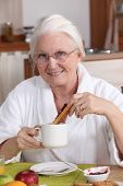 Elderly woman having breakfast