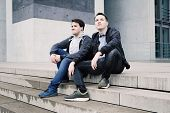 Two Male Teenage Friends Or Brothers Two Male Teenage Friends Sitting On Concrete Steps Or Staircase poster