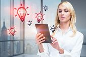 Serious Blonde Businesswoman Working With Tablet In Panoramic Office With Light Bulbs Drawn Around H poster