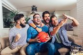 Happy Friends Or Basketball Fans Watching Basketball Game On Tv And Celebrating Victory At Home.frie poster