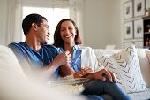 Young adult mixed race couple sitting on the sofa in their living room laughing and eating popcorn,  poster