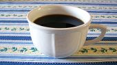 Cup Of Coffee On Striped Table Cloth