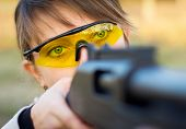 stock photo of girls guns  - A young girl with a gun for trap shooting and shooting glasses aiming at a target - JPG