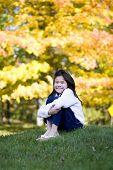Little Girl Hugging Knees Sitting On Lawn, Autumn