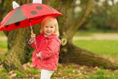 Portrait Of Smiling Baby With Red Umbrella Outdoors
