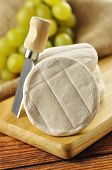 stock photo of tomas  - Italian tomino cheese on a wooden chopping board italian appetizer - JPG