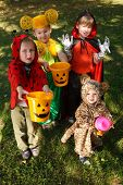 stock photo of greed  - Four boys in halloween costumes trick or treating - JPG