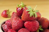 closeup of a pile of appetizing strawberries in an earthenware bowl