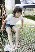 Portrait Of Young Little Cute Smiling Girl Sitting In Hammock. Summer Time.
