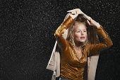 Junge geschäftsfrau über Kopf mit Jacke während Gewitter
