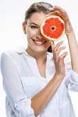 Young beautiful woman with the slice of grapefruit in front of her eye isolated on white background