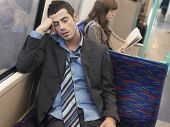 stock photo of coat tie  - Businessman with loosened tie sleeping in commuter train - JPG