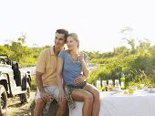 stock photo of  jeep  - Young couple at picnic during safari with jeep in the background - JPG