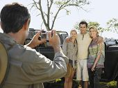 picture of  jeep  - Man taking photograph of three friends against jeep - JPG