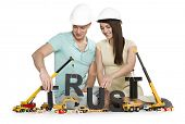 Building up trust concept: Happy young man and woman along with construction machines establishing t