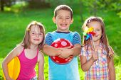 stock photo of frisbee  - Three smiling kids in a summer park - JPG
