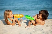Kids having fun with water pistols on the beach - playing in the sand
