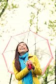 Asian woman in Autumn happy with umbrella in rain. Female model looking up at clearing sky joyful on