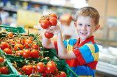 menino criança durante as compras com legumes tomate vermelho maduro no supermercado