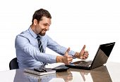 Young modern businessman excited with his success giving thumbs up to the laptop