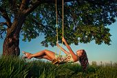 Beautiful girl on the swing in the forest