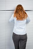 picture of snoopy  - A young businesswoman assistant or an employee peeking through closed window blinds - JPG