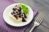 stock photo of banana split  - Sliced banana with melted chocolate and kiwi on plate closeup - JPG