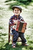 stock photo of accordion  - Happy young boy playing accordion in summer - JPG