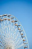 Ferris Wheel Over The Blue Sky