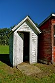pic of outhouse  - A door to an old white outhouse is half open where it stands next to a red shed - JPG