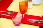 Table Serving With Wine Glasses And Bright Napkins In Street Cafe