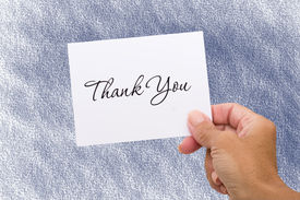 stock photo of thank you note  - A hand holding a thank you card on a blue background thank you card - JPG