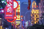 SHANGHAI, CHINA - JUNE 16, 2014: Neon signs lit on Nanjing Road. The street is the main shopping roa