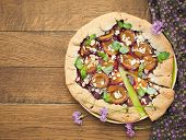 A tart with plums on wooden background.