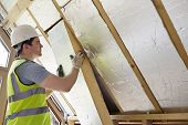 stock photo of insulator  - Builder Fitting Insulation Into Roof Of New Home - JPG