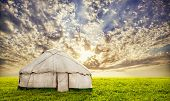 stock photo of nomads  - Urta nomadic house on the grass field at sunset evening sky in central Asia - JPG