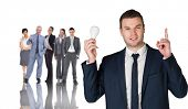 Composite image of businessman holding light bulb and pointing against group of workers