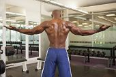 Rear view of a shirtless bodybuilder with arms outstretched in gym