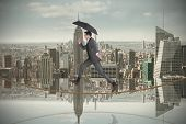Businessman jumping on tightrope holding an umbrella against room with large window looking on city