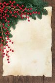 Christmas and winter background border with fir and red ball decorative sprays over old parchment pa