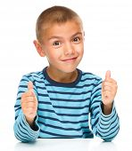 Portrait of a cute boy showing thumb up sign using both hands, isolated over white