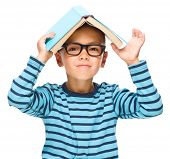 Cute little child plays with book while wearing glasses, isolated over white