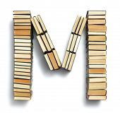 Letter M formed from the page ends of closed vintage hardcover books standing on a white background