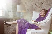 Fashion glamour girl dreamily sitting in white chair in violet lace dress.