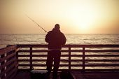 Fishing in the ocean from a pier in early morning.