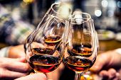 stock photo of cheer  - Group of friends a toast to the cheers of cognac or brandy - JPG