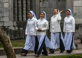 Four Young Vietnamese Nuns In Ao Dai Going To Church Service.