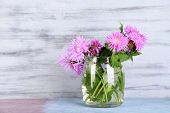Cornflowers in glass jar on wooden background