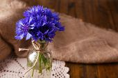 Beautiful cornflowers in glass vase on wooden background